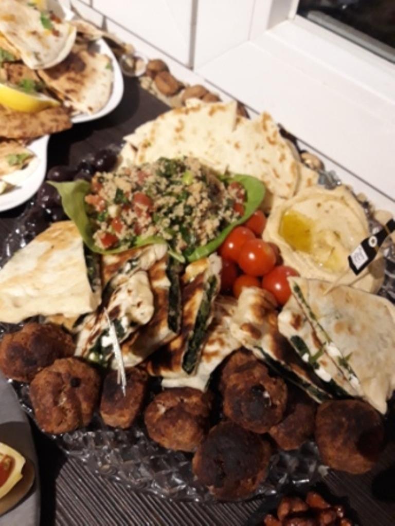 Platte mit Hummus, Frikadellen, Tabuleh, Gözleme und Fladenbrot