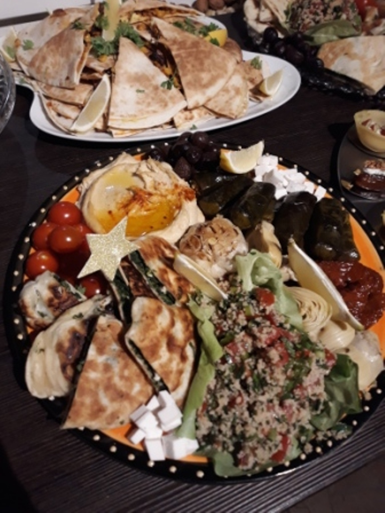 Platte mit Tabuleh, Gözleme, Hummus, gefüllten Weinblättern und eingelegtem Gemüse