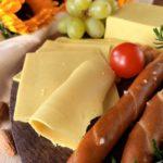 Veganer Schnittkeese auf einem Brett mit Salzstangen und Trauben.
