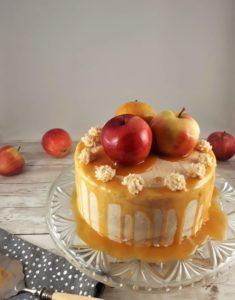 Hellbraune Karamelltorte auf einer Glasplatte. Am Rand der Torte läuft goldgelbes Karamell herunter. Obenauf liegen drei Karamelläpfel.