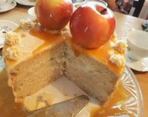 Anschnitt Apfel-Karamell-Torte. Drei Böden heller Biskuit. Dazwischen eine Schicht beige Karamellsahne und eine Schicht Äpfelstücke. Obenauf liegen zwei Karamelläpfel.