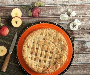 Apple Pie mit Gitter- und Blumenmuster auf einer orangen Platte. Daneben liegen ein Messer, Äpfel und Ausstecher.