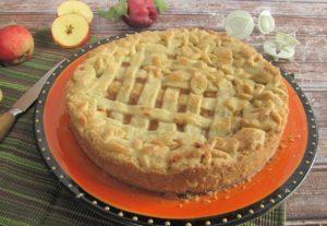 Apple Pie mit Gitter- und Blumenmuster auf einer orangen Platte. Im Hintergrund liegen Messer, Äpfel und Ausstecher.