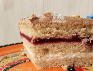 Angeschnittene Torte mit mehreren Schichten. Drei helle Biskuitböden mit einer weißen Sahneschicht und einer roten Fruchtschicht dazwischen.