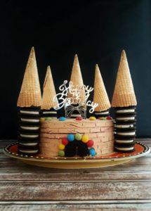 Braune Torte mit vier Türmen aus schwarz-weißen Keksen, die von Eiswaffeln gekrönt werden. Vorne befindet sich eine Tür aus zerbrochenen schwarzen Keksen, die von Schokolinsen umrahmt sind.