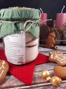 Ein großes Glas mit Lebkuchenbackmischung steht auf einem weihnachtlich dekorierten Holzuntergrund. Eine Backanleitung ist auf das Glas geklebt. Im Vordergrund liegen verzierte Lebkuchen.