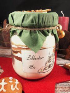 Ein großes Einmachglas mit Lebkuchenbackmischung steht auf einem Holzuntergrund. Drumherum liegen Lebkuchenplätzchen und kleine goldene Christbaumkugeln.