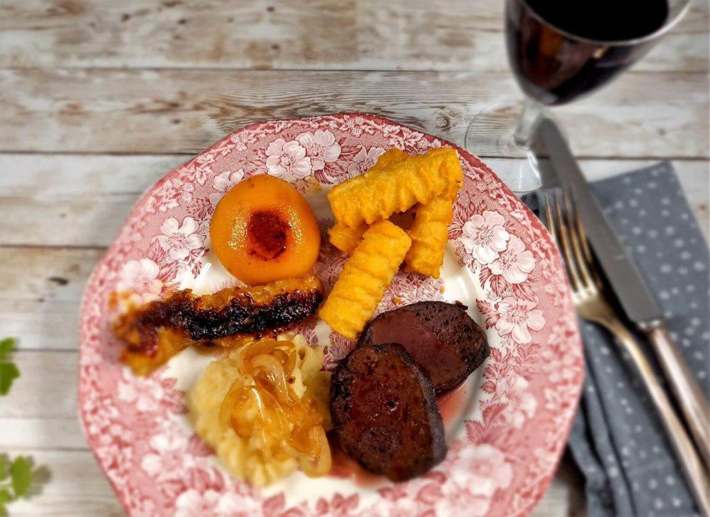 Seitanfilets, Kroketten, Selleriepüree und gebratenes Obst auf einem Teller.