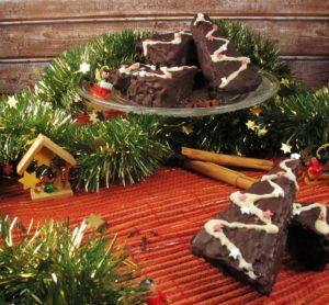 Lebkuchenecken liegen auf und vor einer Glasplatte mit Sockel. Unter der Platte liegt eine grüne Tannengirlande und Baumanhänger aus Holz.