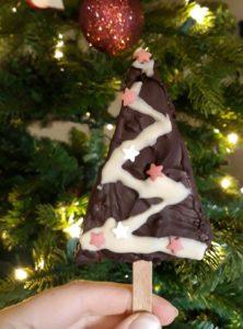 Eine Hand hält eine Lebkuchenecke am Stiel, die wie ein stilisierter Weihnachtsbaum dekoriert ist. Im Hintergrund steht ein beleuchteter Tannenbaum.