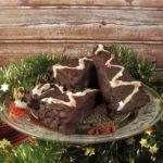 Lebkuchenecken, die mit Schokolade überzogen sind, liegen auf einer Glasplatte mit Sockel. Darunter liegt eine Tannengirlande mit goldenen Sternen.