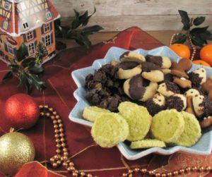 Pistazientaler auf einem Teller mit anderen Weihnachtsplätzchen auf einen Tisch mit weihnachtlicher Deko.