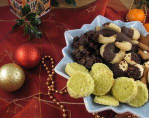 Pistazientaler mit anderen Weihnachtsplätzchen in einer Schale auf einem  weihnachtlich dekorierten Tisch.