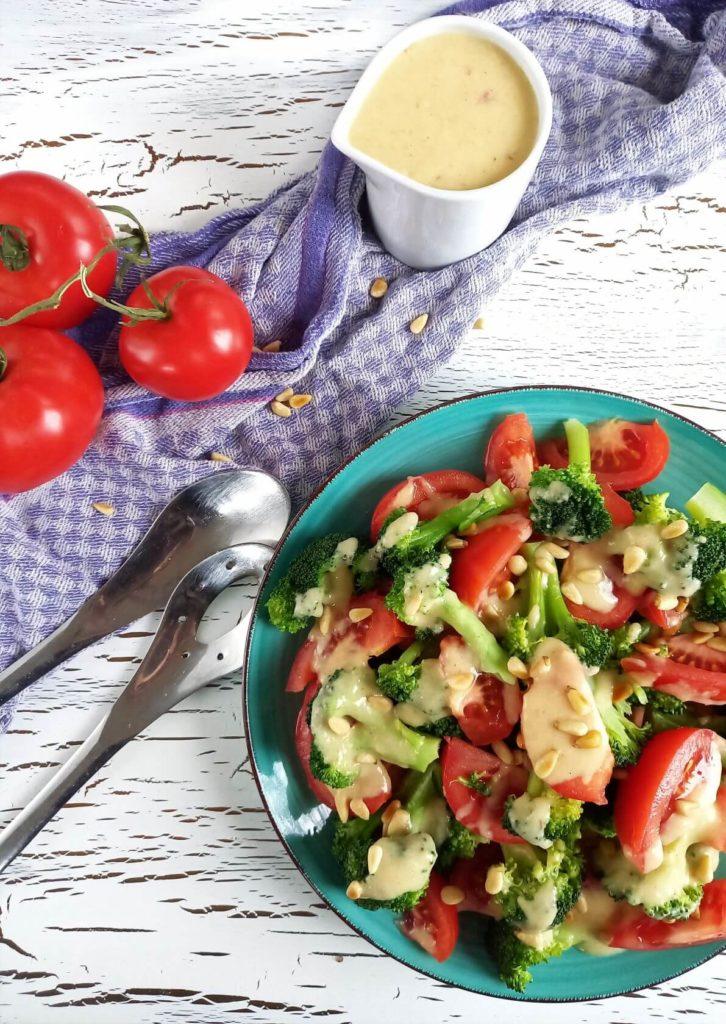 Brokkoli-Tomaten-Salat auf einem Teller. Daneben ein Tuch, Tomaten und ein Kännchen mit Sauce.