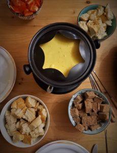 In einem Fonduetopf befindet sich eine cremige Keesemasse. Rundherum stehen Schalen mit Brot- und Paprikawürfeln.