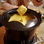 Ein Brotwürfel wird in eine cremige Keesemassse getunkt, die sich in einem Fonduetopf befindet.