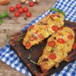 Zwei Pizzabaguettes liegen auf einem Holzbrett auf einer karierten Tischdecke. Darum liegen Tomaten und eine Zwiebel.