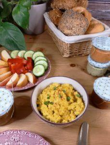 Rührtofu in einer Schale auf einem gedeckten Frühstückstisch.