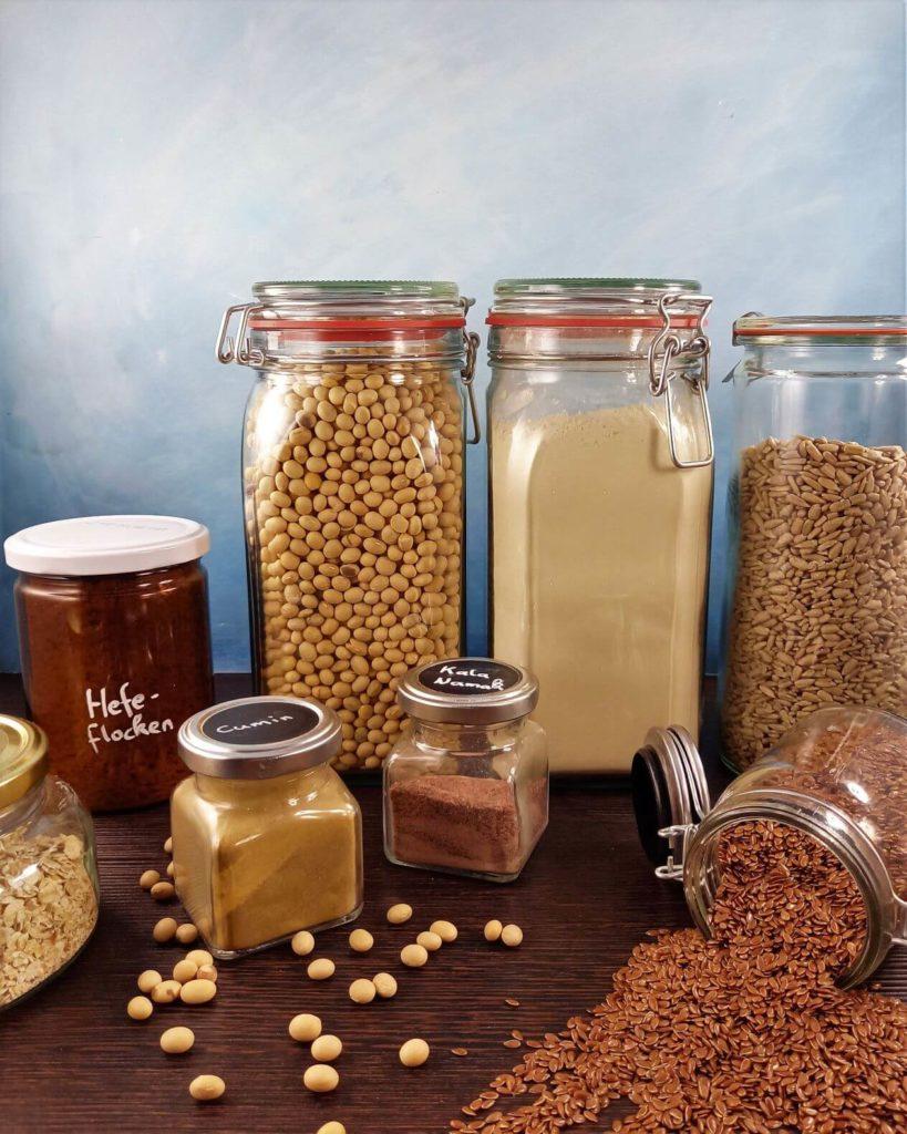 In verschiedenen Aufbewahrungsgläsern befinden sich Bohnen, Mehle und Körner.
