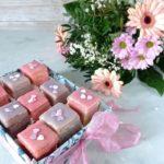 Mehrere rosa und lila Petit Fours in einer Box mit Schleife. Im Hintergrund liegt ein Blumenstrauß mit rosa Blumen.