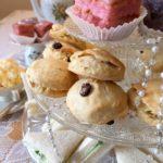 Scones, Sandwiches und Petit Four auf einer Etagere auf einer Kaffeetafel. Daneben Marmelade, und vegane clotted cream.