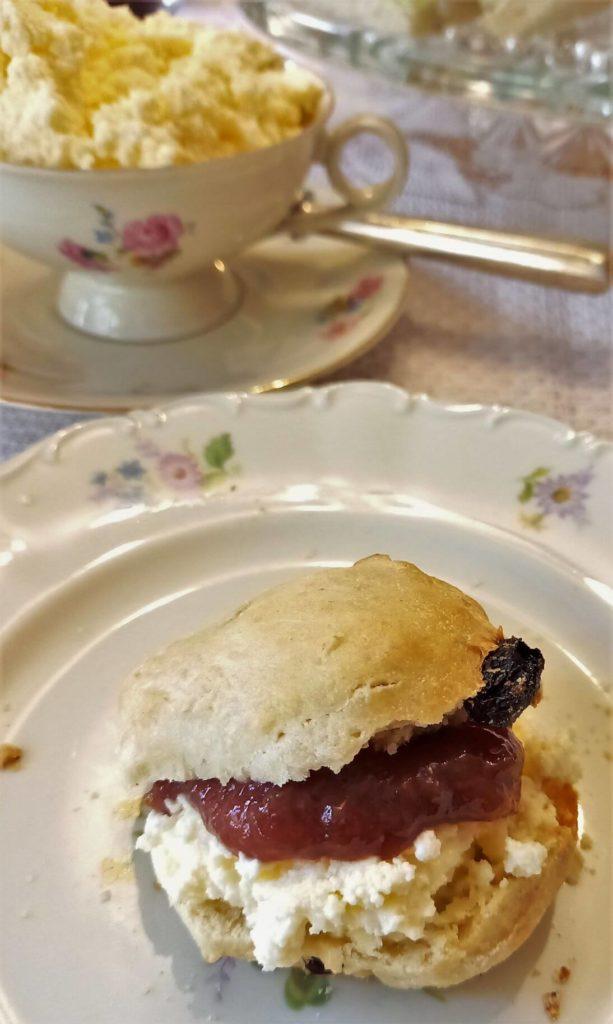 Scone mit clotted cream und Marmelade auf einem Teller.
