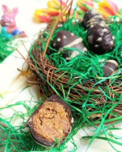 Mehrere Blätterkrokanteier in einem Osterkörbchen mit Ostergras. Davor liegt ein angebissenes Blätterkrokantei.