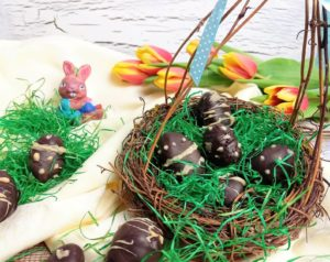 Mehrere Blätterkrokanteier in und neben einem Nest mit Ostergras.
