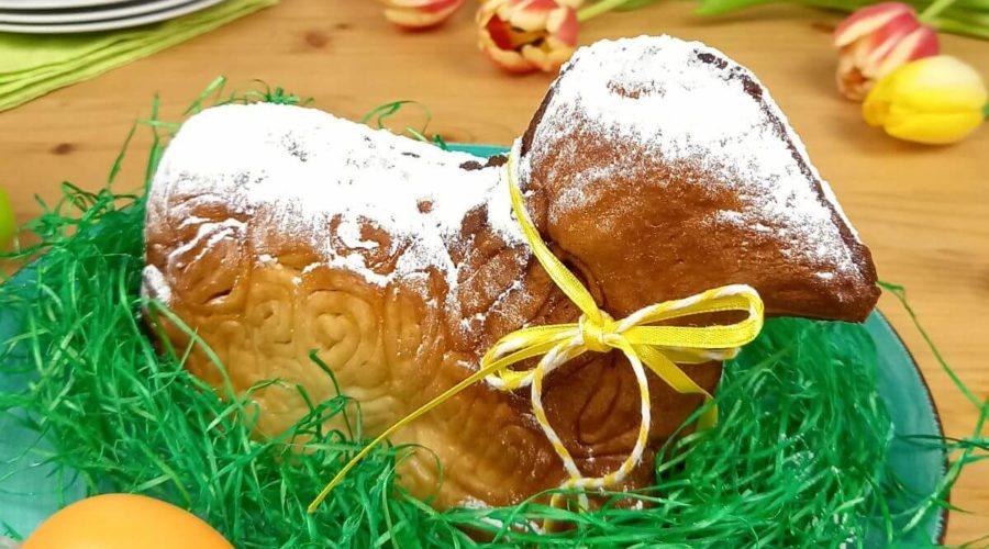 Osterlämmchen in Ostergras sitzend.