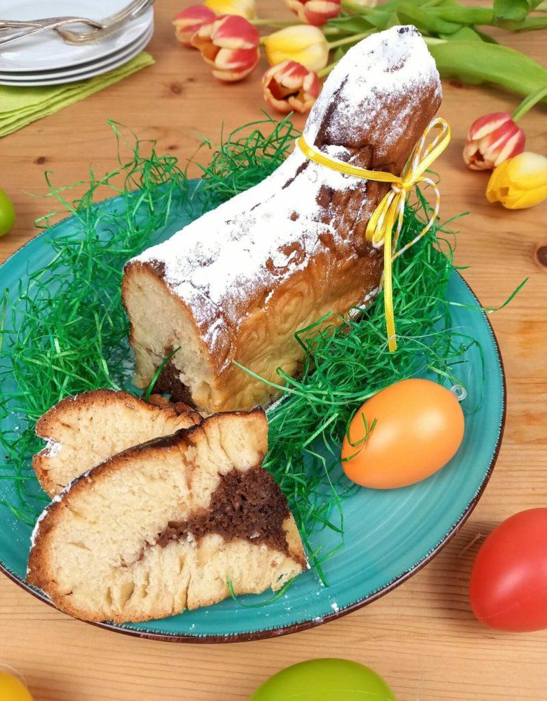 Aufgeschnittenes Osterlämmchen auf einem türkisen Teller.