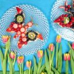 Obstboden in Schmetterlingsform belegt mit verschiedenen Beeren vor einem hellblauem Hintergrund. Am unteren Rand sind Tulpen zu sehen.