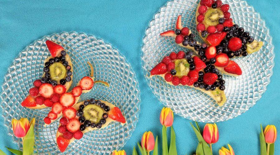 Zwei Obstböden in Schmetterlingsform belegt mit verschiedenen Beeren vor einem hellblauem Hintergrund. Am unteren Rand sind Tulpen zu sehen