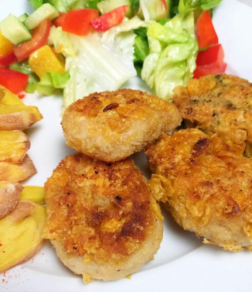 Nuggets auf einem Teller mit Salat und Ofenkartoffeln.