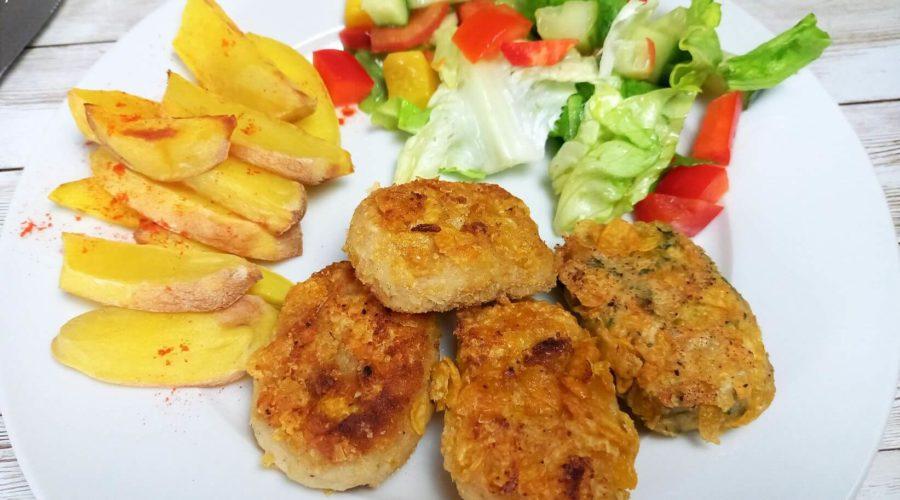 Bohnen-Nuggets auf einem Teller mit Ofenkartoffeln und Salat.