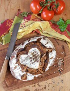 Brotlaib auf einem Brett neben einem Messer, einem Küchentuch und Tomaten.