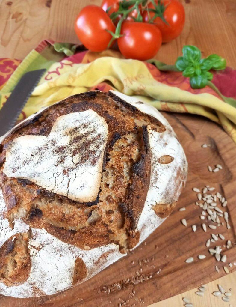 Brotlaib auf einem Brett neben einem Messer, einem Küchentuch und Tomaten