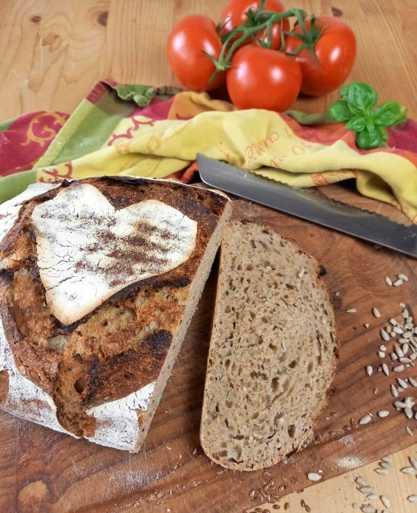 Angeschnittener Brotlaib auf einem Brett neben einem Messer, einem Küchentuch und Tomaten