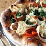 Pizzakeese auf einer mit Gemüse belegten Pizza mit krossem braunem Rand.