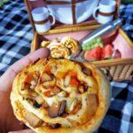 Eine Hand hält eine Pizzaschnecke. Im Hintergrund ist ein Picknickkorb, in dem in je einer Dose Pizzaschnecken und Obst liegen.