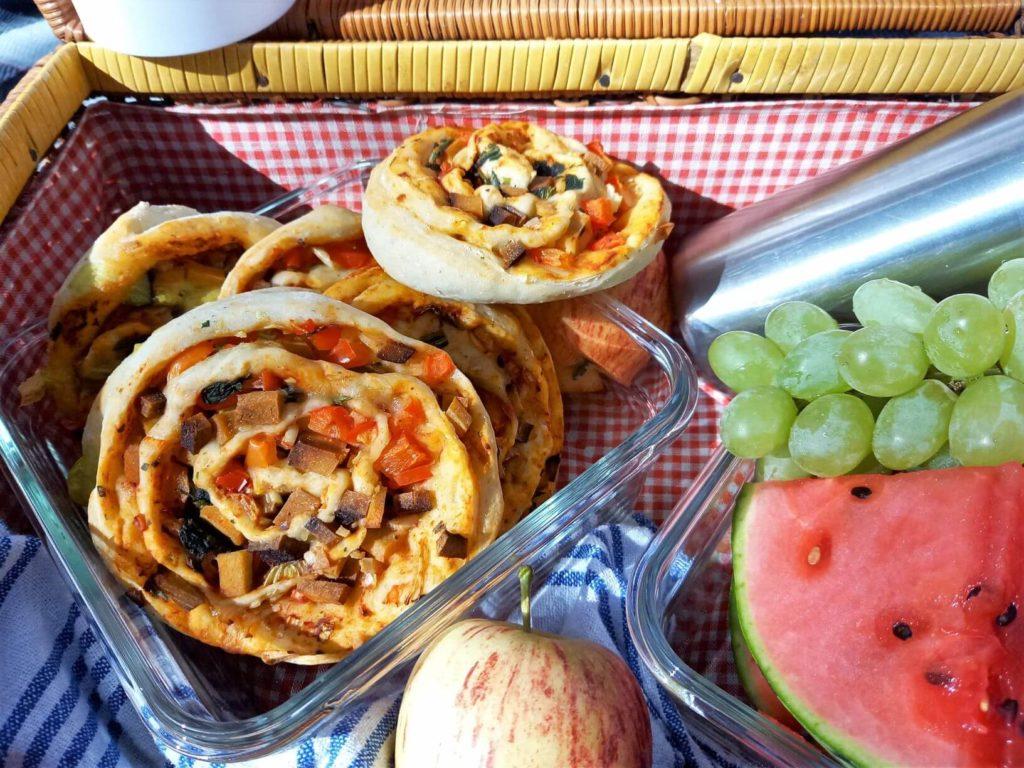 Pizzaschnecken in einer Dose neben Obst. Alles befindet sich in einem Picknickkorb.