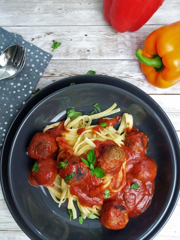 Nudeln mit Tomatensauce und braunen Gemüsebällchen auf einem grauen Teller. Um den Teller liegt eine graue Serviette mit Besteck und eine orange Paprika.