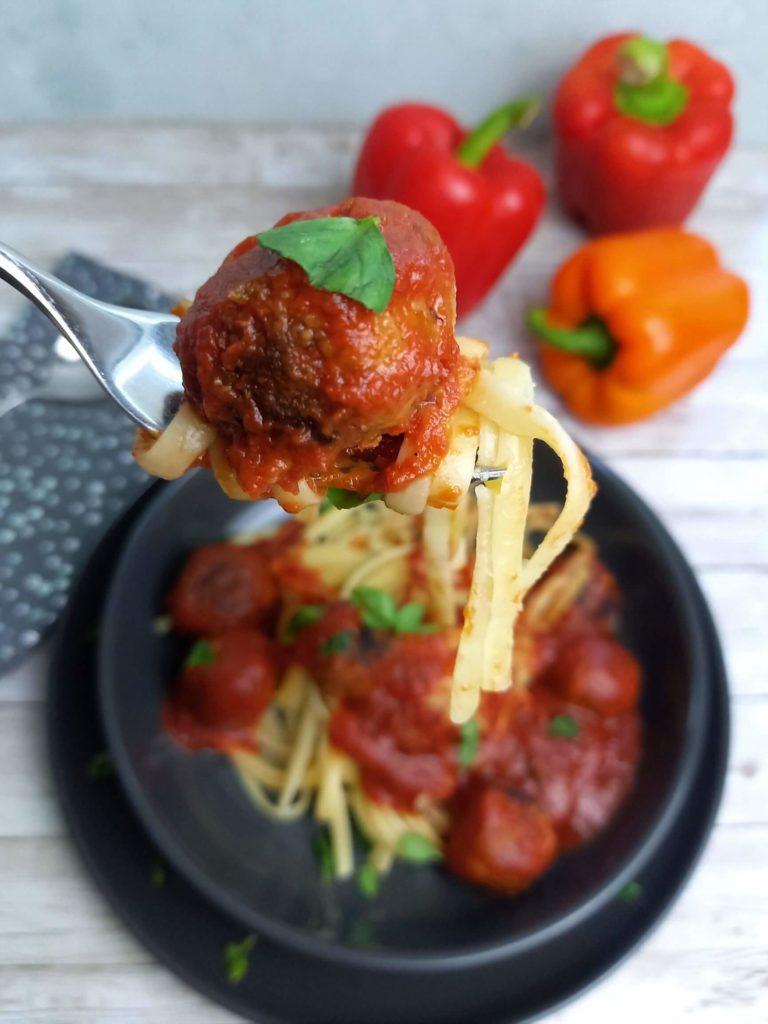 Ein grauer Teller mit Linguini, Tomatensauce und Gemüsebällchen steht auf einem weißen Holztisch. Darüber hält eine Hand eine Gabel auf der sich ein paar Linguini und ein Gemüsebällchen befinden.
