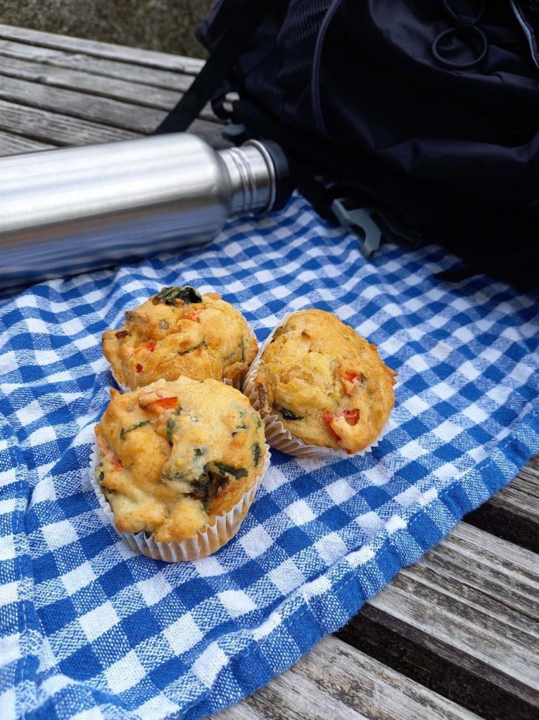 Drei Pizzamuffins liegen auf einem blau-weiß karierten Tuch. Im Hintergrund liegt eine Edelstahlflasche.