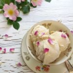 In einer altmodischen Tasse mit Rosenmotiv befinden sich drei Kugeln weißes Eis. Das Eis ist mit getrockneten Rosenblüten dekoriert. Im Hintergrund liegen ein paar Wildrosen.