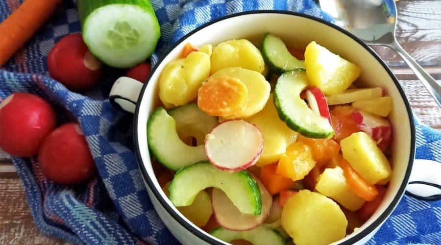Inmitten von Gemüse steht eine Schale mit buntem Kartoffelsalat.