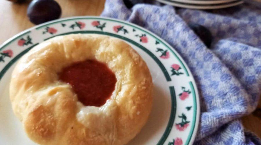 Auf einem Teller liegt ein Teigkringel mit Kompottfüllung. Im Hintergrund ist ein weiterer Kringel, sowie ein Schälchen mit Kompott und ein paar Zwetschgen zu sehen.