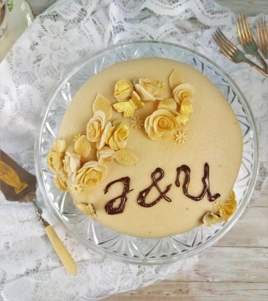 Marzipantorte mit Rosendekor auf einer weißen Spitzendecke. Im Hintergrund liegen Gabeln, Teetassen und ein Tortenheber.