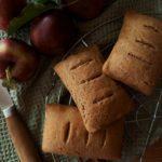Drei Apfeltaschen liegen auf einem Kuchenrost. Daneben liegen Äpfel.