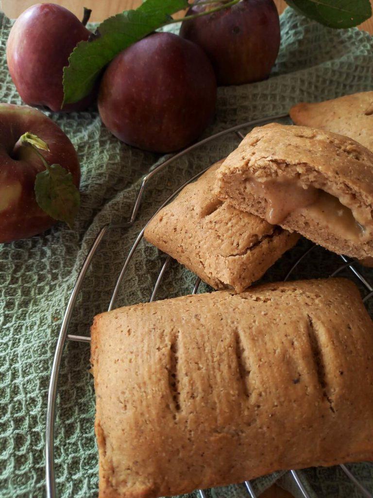 Drei Apfeltaschen liegen auf einem Kuchenrost. Eine ist halbiert. Daneben liegen Äpfel.