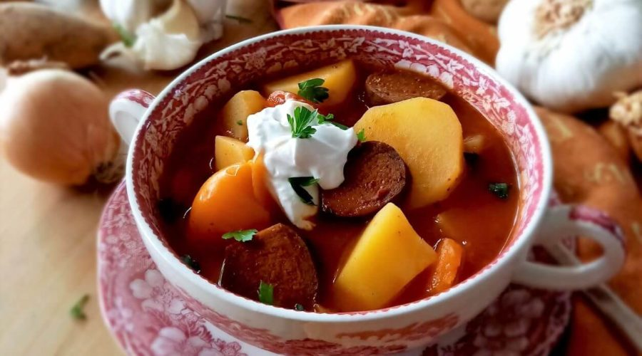 Eine Suppentasse mit Kartoffelgulasch steht auf einem Tisch. Rundherum liegt Gemüse.